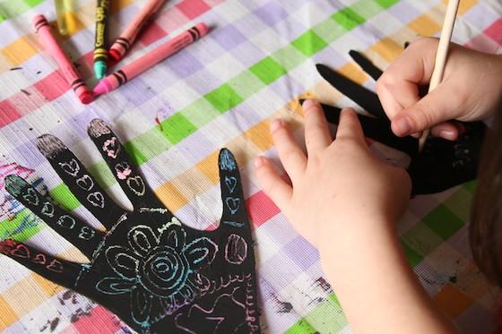 kids making henna hand art with scratch art process