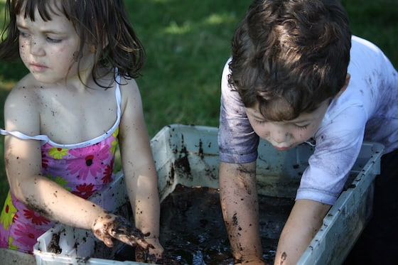 kids playing in a basin of mud