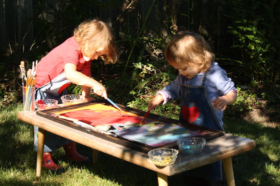 preschooler and toddler painting mirror outside