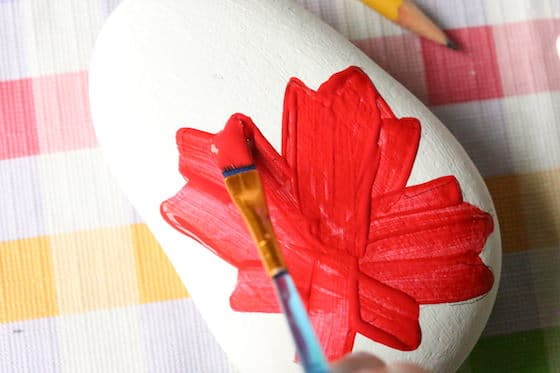 Painting a red maple leaf on a beach rock