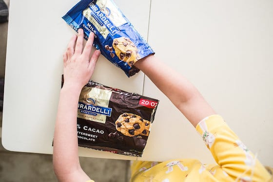 child putting hand inside bag of chocolate chips