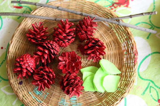 bowl of painted red pinecones and green felt leaves