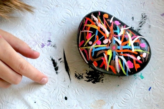Rock painted black and decorated with liquid chalk markers