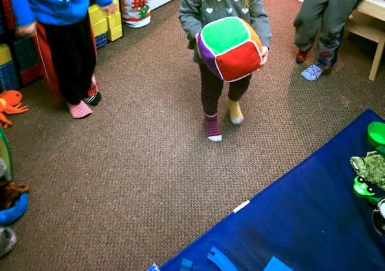 Child rolling large coloured dice