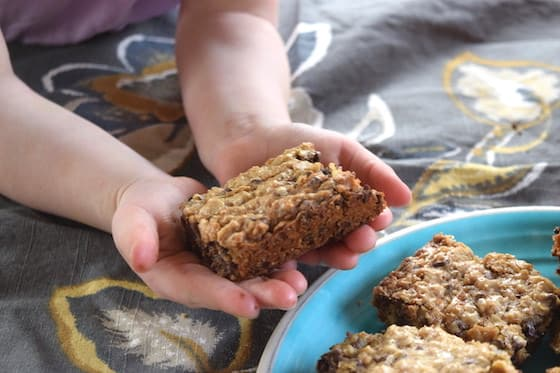 toddler holding homemade oatmeal bars with chocolate chips