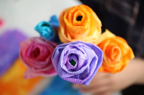 Child holding purple, pink, blue and yellow paper towel roses