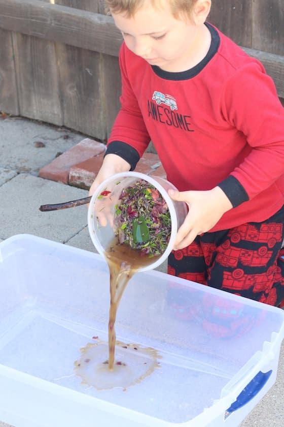 preschooler dumping water into shallow bin
