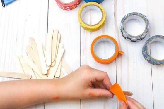Child taping craft stick