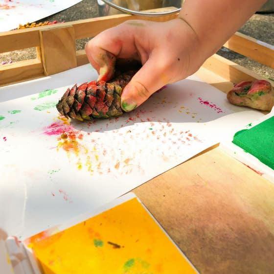 childs hand making pinecone print