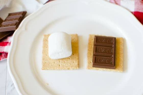graham cracker with marshmallow and hershey's bar on white plate