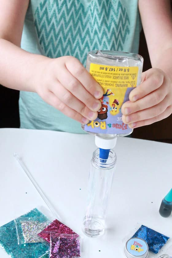 squeezing glue into glitter bottle