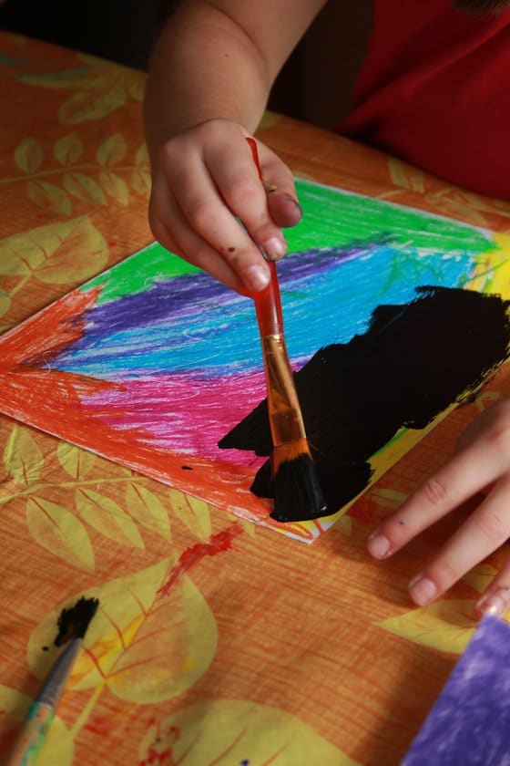 kids painting over pastels with black paint