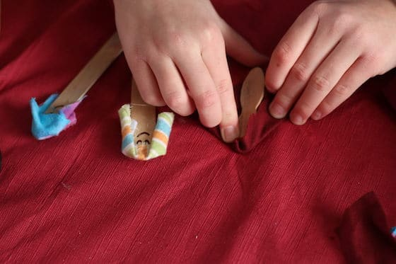 child wrapping popsicle stick in fabric