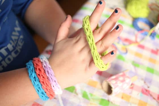 child modeling french knitted bracelets
