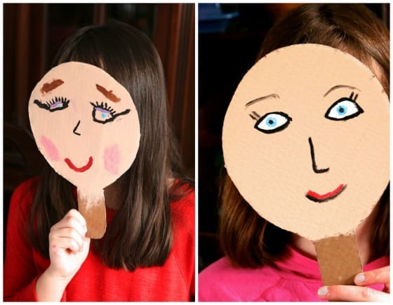 Kids holding homemade puppet paddles up to their faces