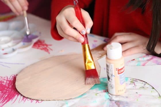 Child painting base coat on cardboard puppet