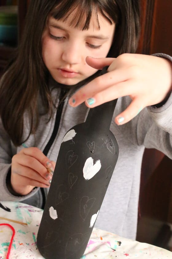 child painting hearts on wine bottle