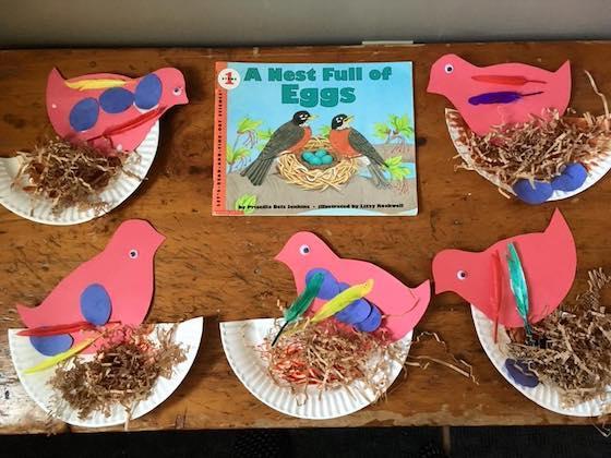 construction paper birds and nests beside preschool bird book
