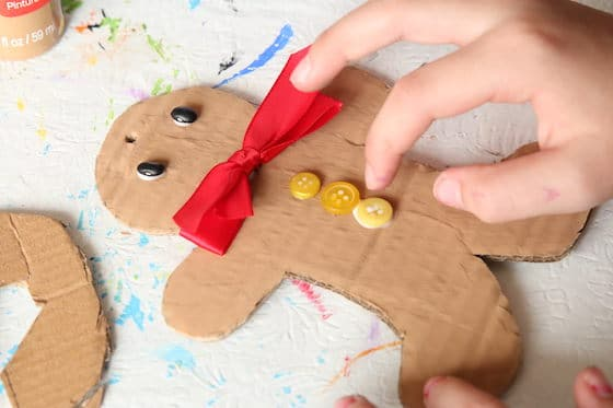 gluing buttons on gingerbread man