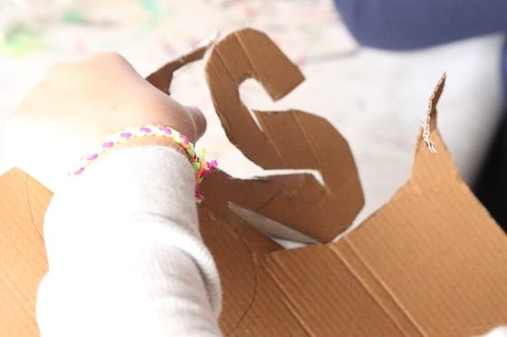 Child cutting letter S out of cardboard