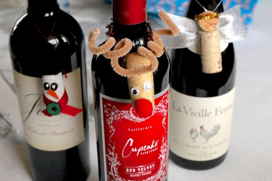 Cork snowman, reindeer and angel ornaments hanging on wine bottles
