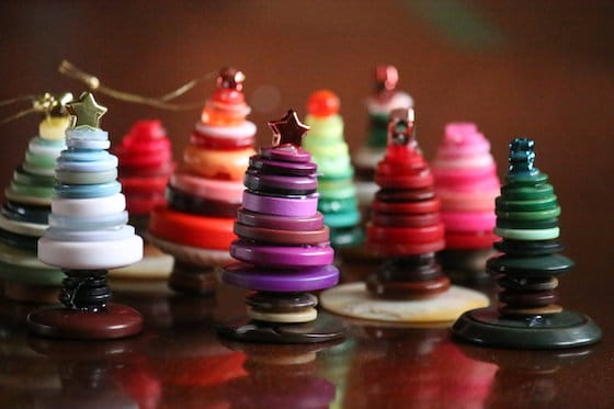 10 Small Christmas tree ornaments made with colourful buttons standing on tabletop