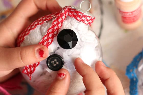 kid gluing buttons on snowman belly ornament with red checkered scarf