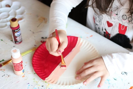 kid painting santa hat and face on paper plate
