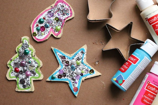 Decorated star, mitt and christmas tree ornaments on piece of cardboard with paint and cookie cutters