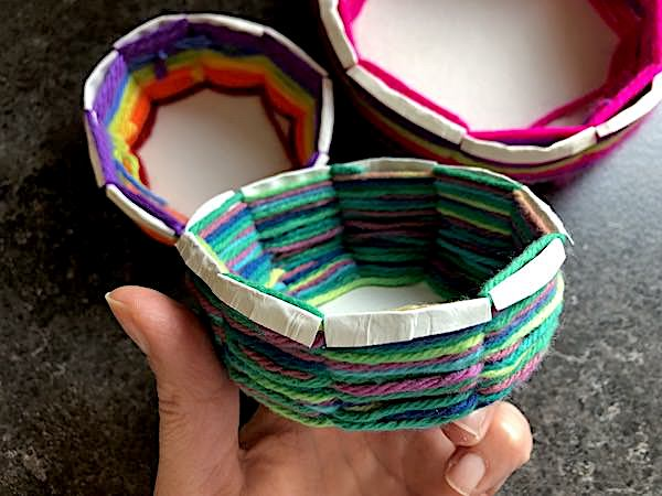 folding edges of paper plate down over weaving