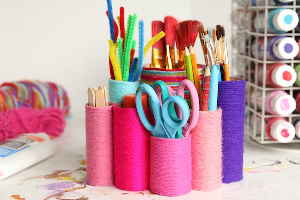 closeup toilet roll organizer wrapped with yarn and filled with supplies