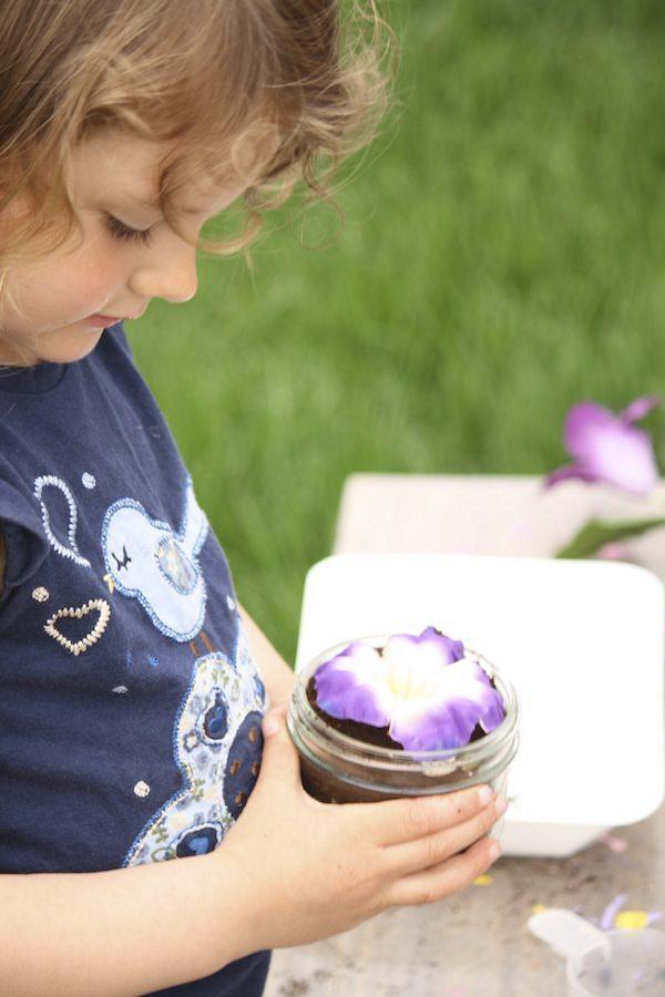 Enfant tenant une fleur artificielle dans un bocal en verre de marc de café