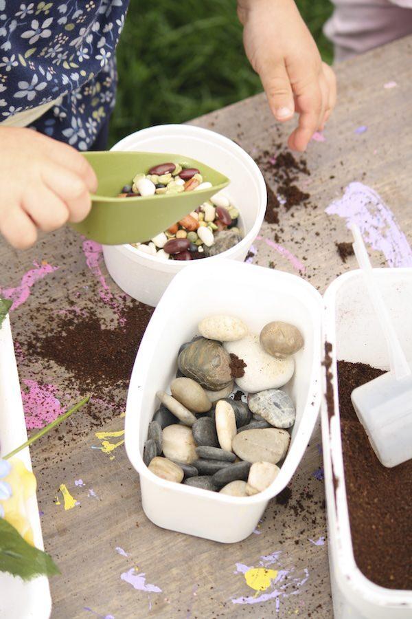 preschooler scooping dried lentils into pretend flower vase