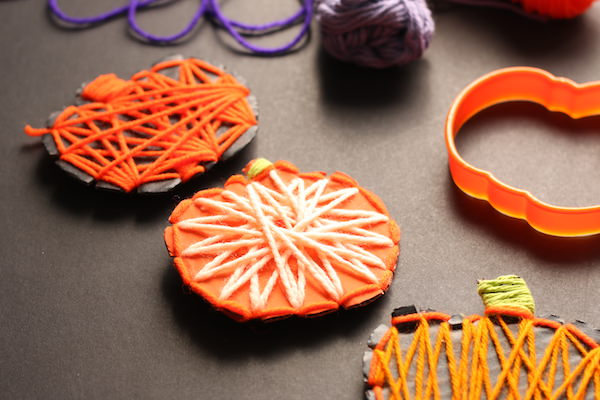 3 cardboard pumpkins wrapped in yarn displayed horizontally on black backdrop