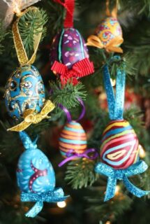 6 ornately painted plastic Easter Eggs hanging on Christmas Tree
