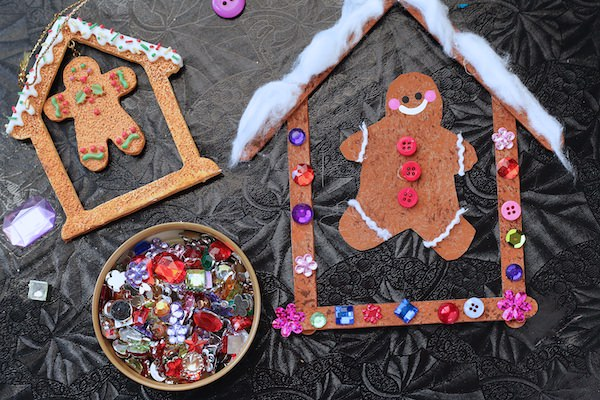 craft stick house and gingerbread cut out decorated with craft gems