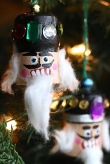 2 cork nutcracker heads on christmas tree, bokeh lights background