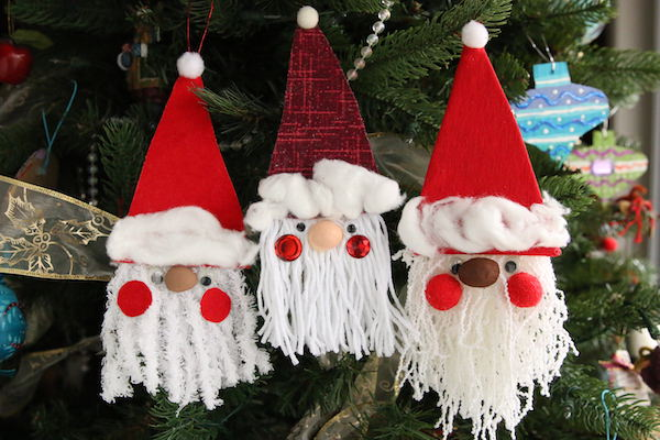 3 yarn and cardboard santas hung horizontally on Christmas tree